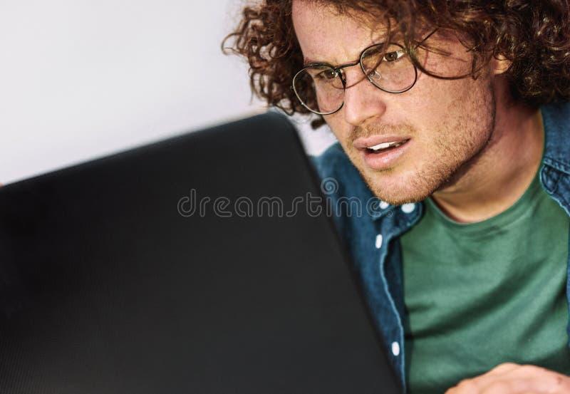 严肃的年轻人学生特写镜头画象有坐在他的有膝上型计算机读书新闻的书桌的卷发的 图库摄影