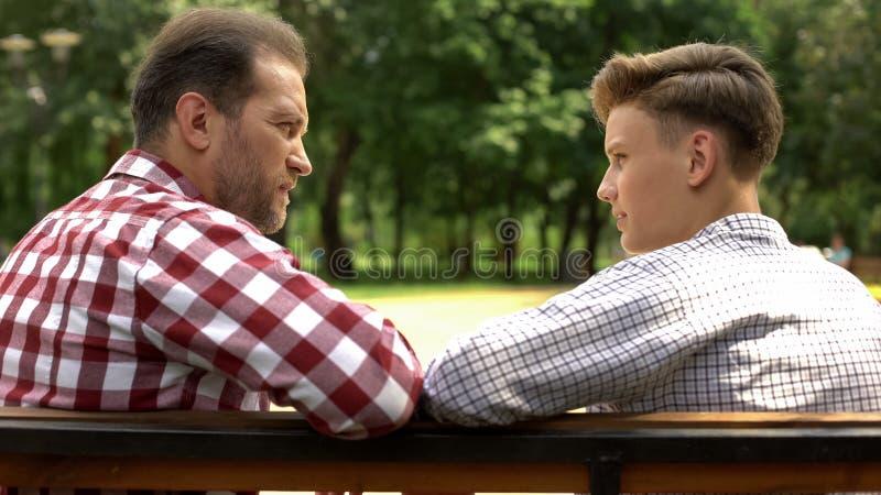 严肃的儿子和爸爸谈话在长凳在公园,分享身世的父亲 库存图片