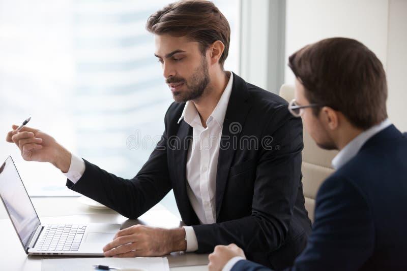 严肃的商人经理谈话与指向膝上型计算机的客户 库存图片