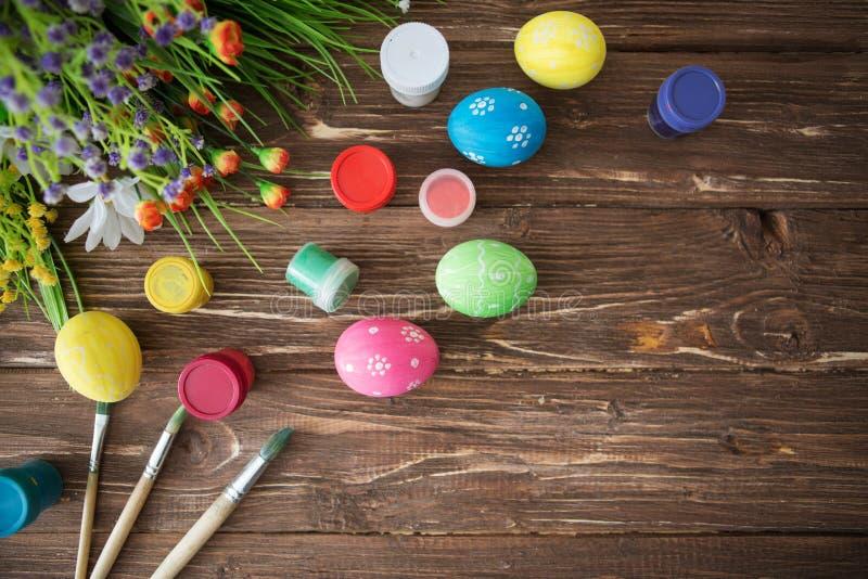 2个所有时段小鸡概念复活节彩蛋开花草被绘的被安置的年轻人 五颜六色的复活节彩蛋、油漆调色板和刷子在木桌上 顶视图 库存图片
