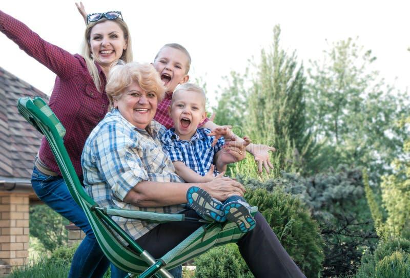3个照相机长沙发系列女孩查找关于坐的母亲橙色纵向他们那里 参观的祖母 免版税库存图片