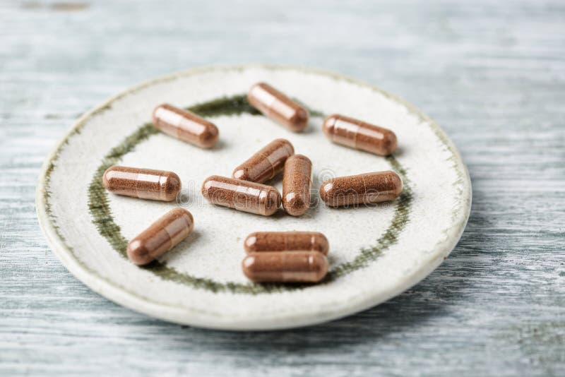 中华的Schisandra 与健康医疗植物的草本胶囊 在土气木背景的健康补充 免版税库存图片
