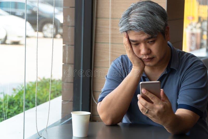 中年亚裔人40岁,被注重和疲倦和使用智能手机,在快速的餐馆坐 在那里桌上 库存图片