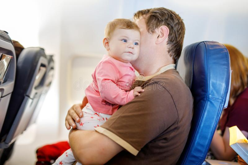 中年父亲和他哭泣的小女儿在飞行期间在继续假期的飞机 使用的爸爸举行和 库存照片