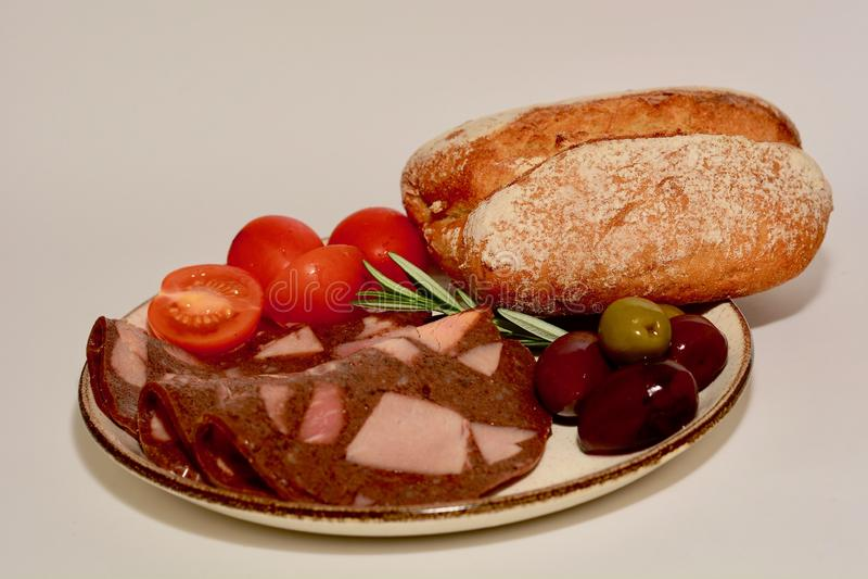 丰盛的一餐或快餐特写镜头照片,包括一些肉糕切片、蕃茄、橄榄和黑麦面包小圆面包  免版税库存照片