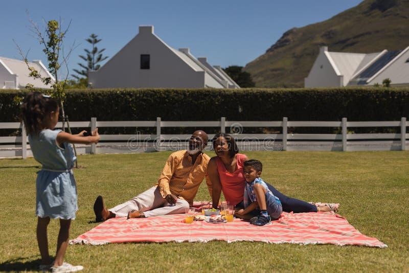 为与手机的女孩多代的家庭照相在后院 免版税库存图片