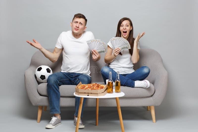 为难的夫妇妇女人足球迷在美元钞票欢呼金钱,现金支持喜爱的队藏品爱好者  库存图片