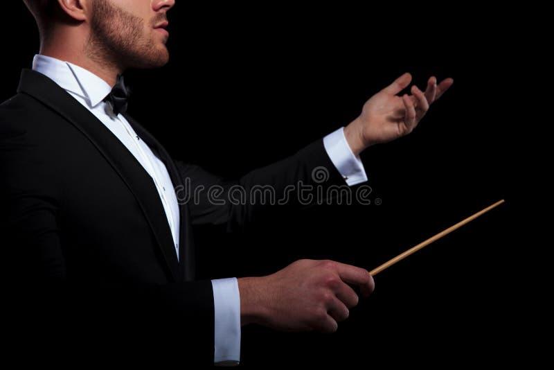 举办使用棍子和打手势的年轻音乐家 库存图片