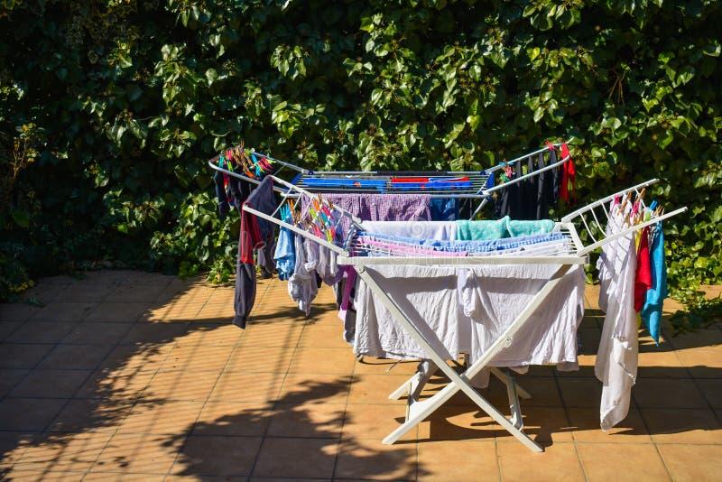 举行在洗涤的线的许多不同的衣裳在一个庭院在一好日子 库存照片