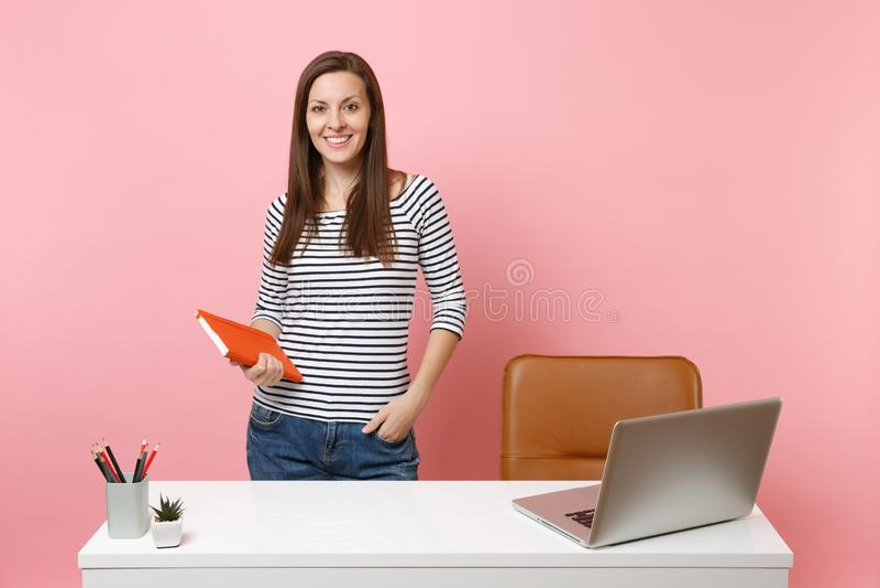 举行笔记本工作身分的便服的年轻成功的妇女在有当代个人计算机膝上型计算机的白色书桌附近 免版税库存图片