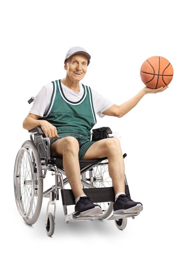 举行篮球和微笑对照相机的轮椅的资深废人 免版税库存照片