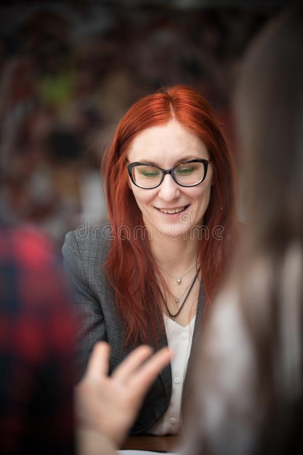 业务会议 微笑的玻璃的一名姜妇女看下来和 免版税库存照片