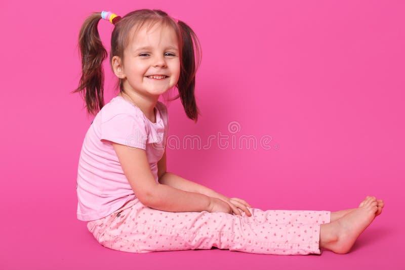 与两马尾和许多五颜六色的scrunchies的俏丽的小孩子坐地板和高兴在照相馆被拍摄 免版税库存图片