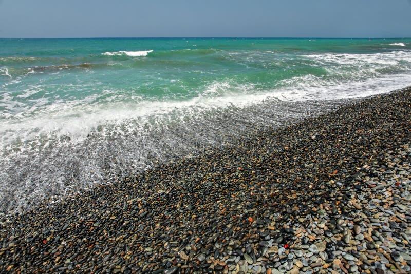 与主要黑暗的小卵石石头、海和天空的狂放的自然海滩在背景中 库存图片