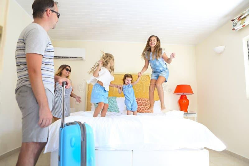 与三个孩子的家庭与行李在酒店房间 免版税库存图片