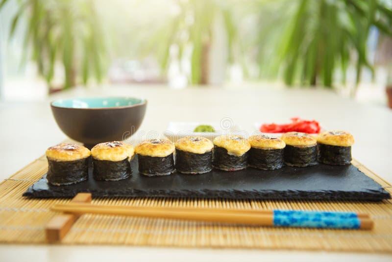 与三文鱼和热的茶道的寿司卷在黑木桌上 与三文鱼,鲕梨,黄瓜的油煎的热的卷 免版税图库摄影