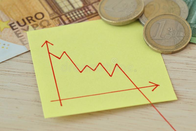 与下降线的图表在纸笔记,欧元硬币和钞票-失去的金钱价值的概念 库存图片