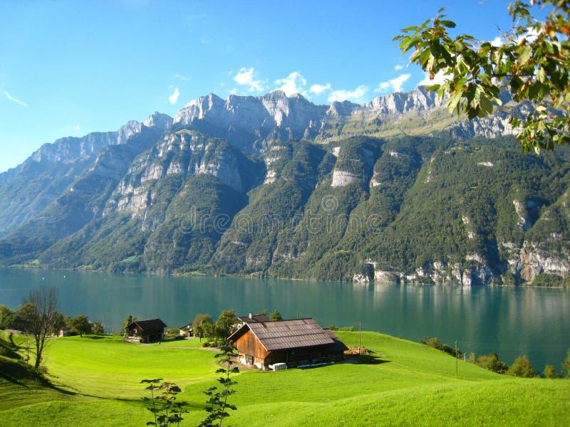 与一个土耳其玉色瑞士湖的美妙全景视图有积雪的山和木房子的 图库摄影