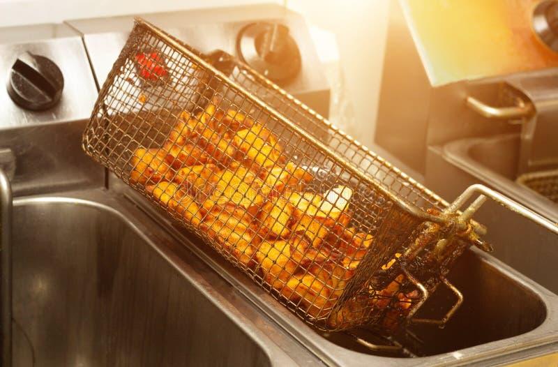 与一个金黄外壳的油煎的土豆,烹调在有许多的一个深炸锅黄油 不健康和肥腻胆固醇食物 库存图片