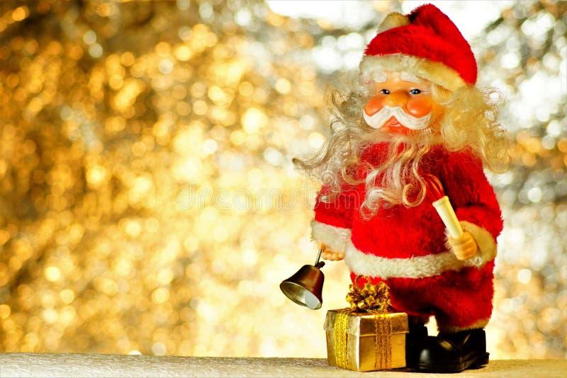 与一件礼物的圣诞老人项目在圣诞灯bokeh背景  圣诞老人项目是给礼物的童话字符 免版税库存照片