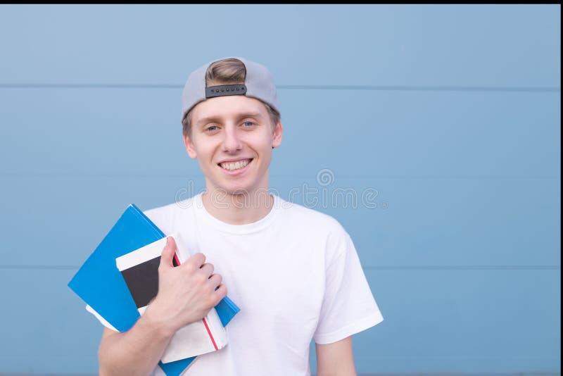 与书的一名愉快的学生的画象白色T恤和盖帽的,立场和notepa 库存照片