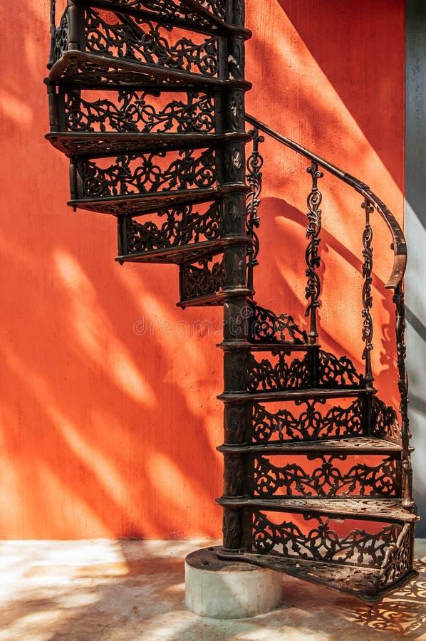 与五颜六色的混凝土墙的葡萄酒锻铁螺旋形楼梯 库存照片