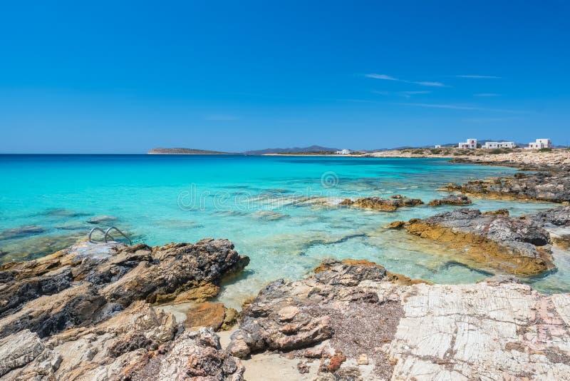与使平静的水惊奇的多岩石的海滩在帕罗斯岛海岛,Cyclade上 免版税库存照片
