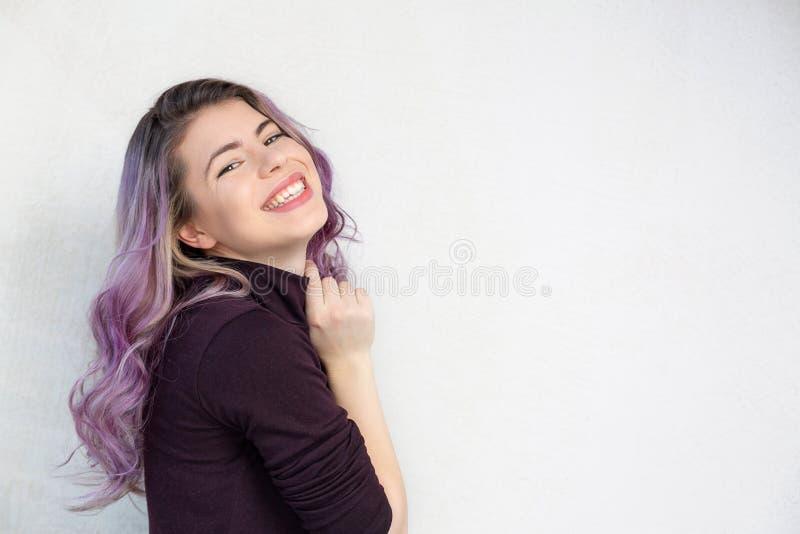 与作梦,在灰色背景的卷曲紫色头发的俏丽的年轻模型 文本的空间 免版税库存图片