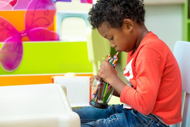 与单独颜色铅笔的黑美国孩子戏剧在幼儿园幼儿园的,教育概念教室 库存照片