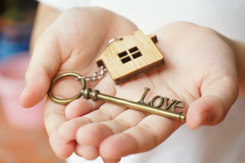 与古色古香的爱形状钥匙的木家庭钥匙圈在woman& x27;s手 对恋人和家庭的一件礼物 家庭甜家庭概念 图库摄影