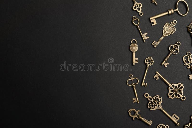 与古铜色葡萄酒华丽钥匙的平的被放置的构成在黑暗的背景 免版税库存图片