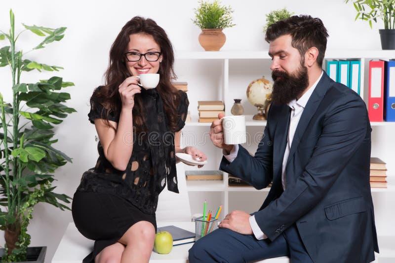 与同事的咖啡休息 在咖啡休息期间的男人和妇女宜人的交谈 谈论办公室谣言 请求  免版税库存图片