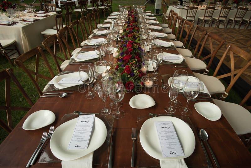 与大自然花和玫瑰焦点的典雅的庭院婚礼桌装饰 免版税库存图片