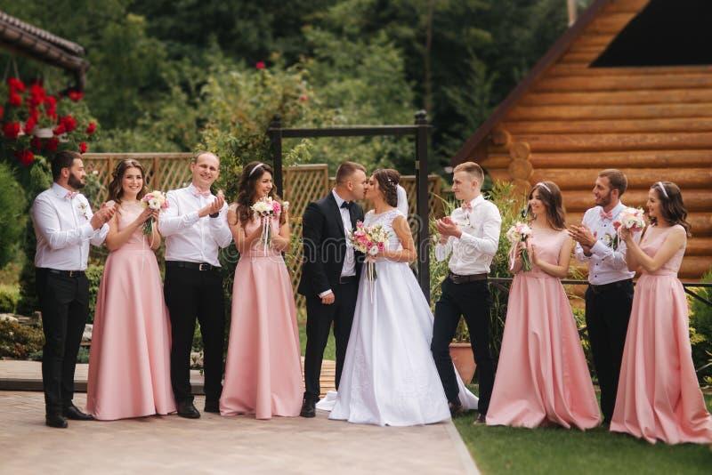 与外面男傧相和女傧相的新郎和新娘立场 亲吻的新婚佳偶和朋友拍手 衣物夫妇日愉快的葡萄酒婚礼 免版税库存图片