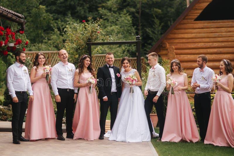 与外面男傧相和女傧相的新郎和新娘立场 亲吻的新婚佳偶和朋友拍手 衣物夫妇日愉快的葡萄酒婚礼 免版税库存照片