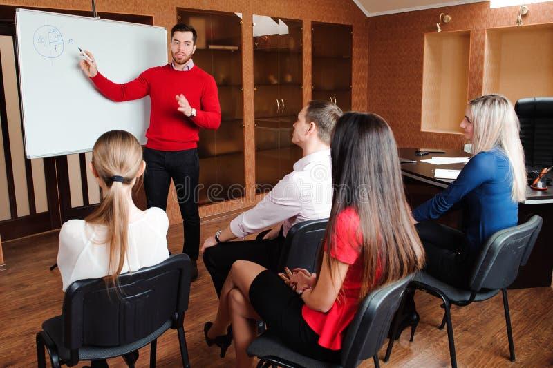 与她的职员的商人,人小组在背景中在户内现代明亮的办公室 库存图片