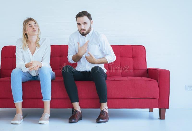 与妻子冲突和乏味的夫妇在客厅,消极情感的丈夫争吵 库存图片