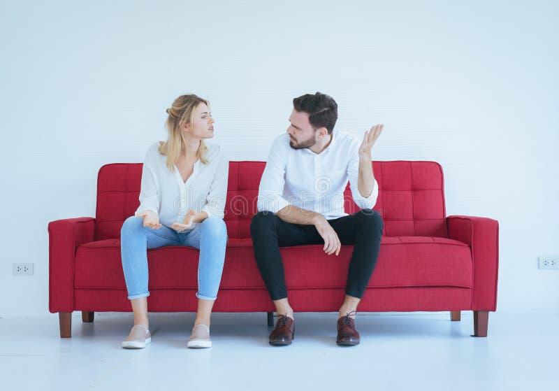 与妻子冲突和乏味的夫妇在红色沙发,消极情感的丈夫争吵 库存图片