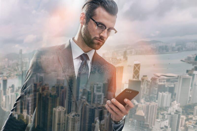 与客户的闲谈 在衣服的英俊的有胡子的商人使用智能手机,当站立反对早晨都市风景时 库存照片