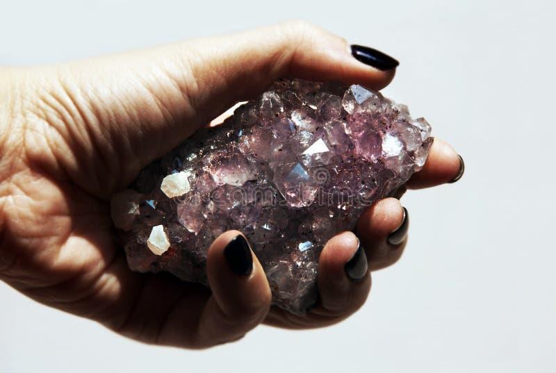 与岩石水晶的手藏品宝石紫色的特写镜头 免版税库存照片