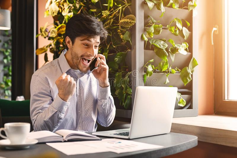 与开放膝上型计算机的激动的千福年的商人谈话在电话 免版税库存照片