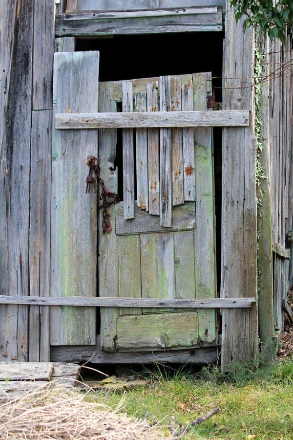 与在后院结构登上的被毁坏的委员会的被即兴创作的部分地残破的老木门锁与生锈的金属链子 免版税库存照片