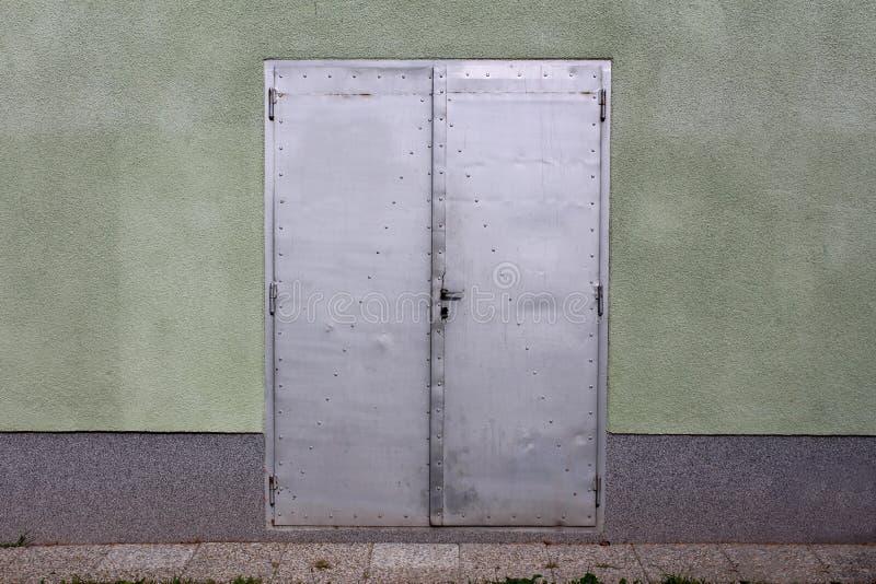与在有石瓦片的房子墙壁登上的小门把手的灰色金属板门在前面 免版税库存图片