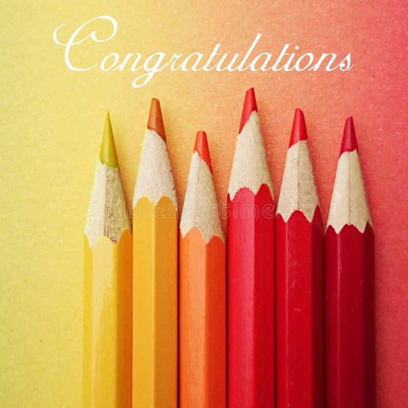 与在颜色安排的六支五颜六色的笔的明信片黄色和红色在五颜六色的纸彩虹其间 免版税库存图片