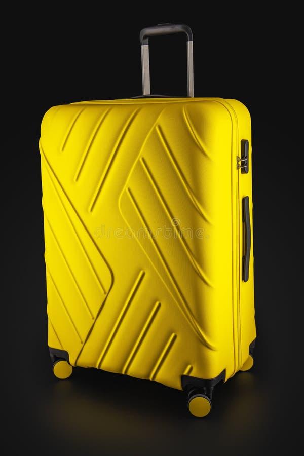 与在黑背景飞行的隔绝的行李的手提箱黄色,裁减路线 免版税库存照片