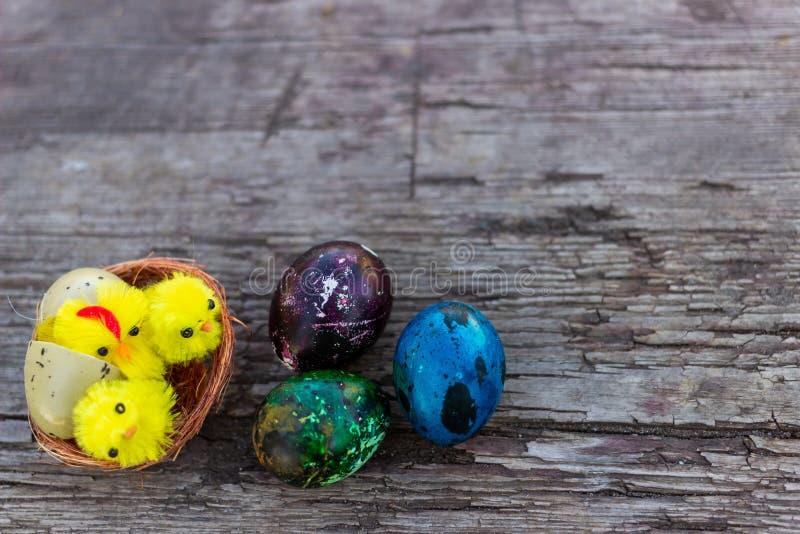 与土气静物画的复活节快乐-与鸟的复活节彩蛋在一个老木板筑巢 春天,复活节概念 库存图片