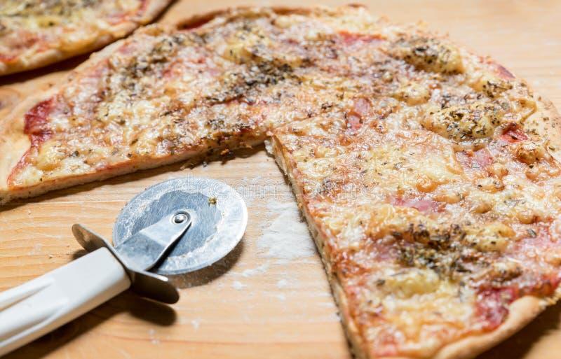 与圈子切削刀刀子在木桌选择聚焦,食物背景的一国内比萨 免版税库存图片