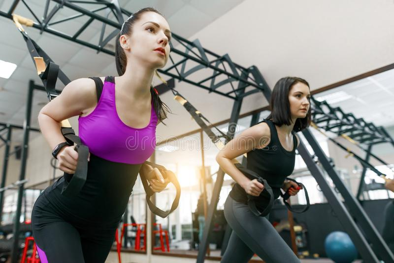 与圈在健身房,做发怒符合皮带系统的两名年轻可爱的健身妇女的小组训练 体育,配合, 库存照片