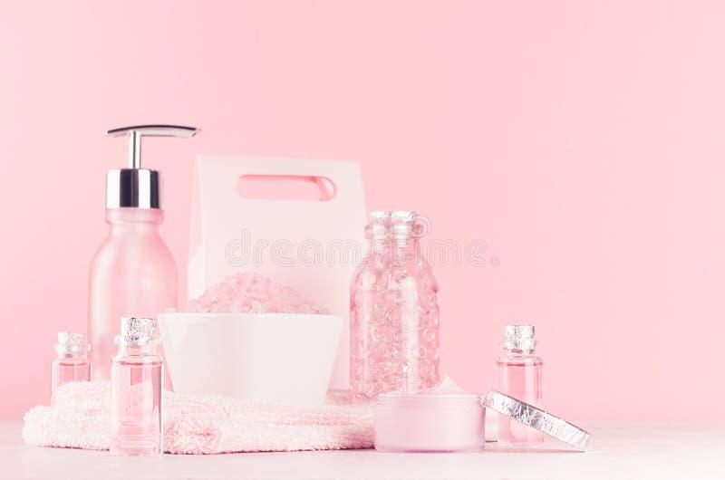 与化妆用品产品的柔和的少女梳妆台-玫瑰油、腌制槽用食盐、奶油、香水、棉花毛巾、瓶和碗 库存图片