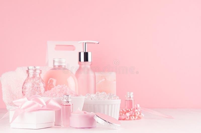与化妆用品产品的柔和的少女梳妆台-玫瑰油,腌制槽用食盐,奶油,香水,棉花毛巾,瓶,碗,箱子 库存照片